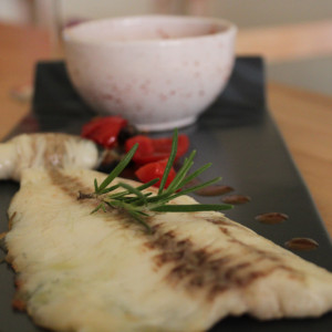 Baked fillet of sea bass with cherry tomato sauce